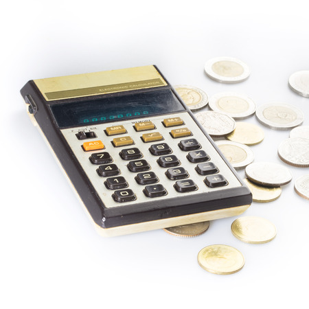 Old calculator and coins, isolated on white photo