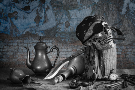 Still life, pirate skull with cigar in the mouth on the log, compass on ancient map, knife brass tea pot and pocket watch with grunge wall background photo