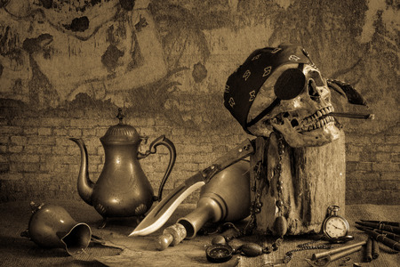 swashbuckler: Still life, pirate skull with cigar in the mouth on the log, compass on ancient map, knife brass tea pot and pocket watch with grunge wall background