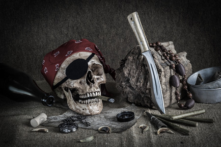 Still life, pirate skull with cigar in the mouth, compass on ancient map, knife and pocket watch hang on the log photo
