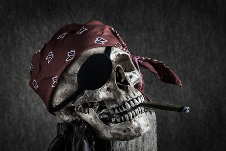 plunder: Still life, pirate skull with cigar in the mouth, compass on ancient map, knife and pocket watch hang on the log