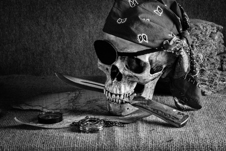 Still life, pirate skull with knife in the mouth, compass on floor and pocket watch hang on the log Stock Photo