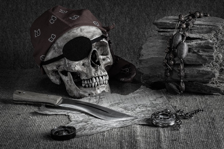 Still life, pirate skull with knife in the mouth, compass on floor and pocket watch hang on the log photo