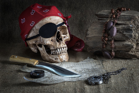 Still life, pirate skull with knife in the mouth, compass and pocket watch on floor Stock Photo