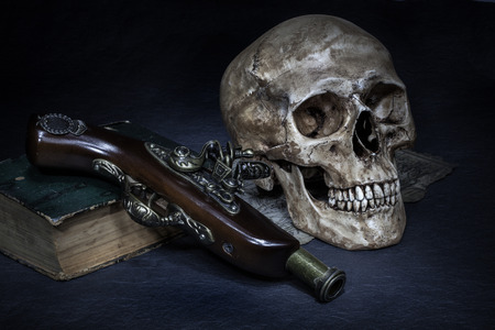 Still life, skull with ancient gun and old book on map photo