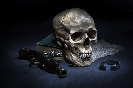 Still life, skull with ancient gun, silver barcelet and old book on map photo