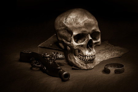 anklet: Still life, skull with ancient gun, silver barcelet and old book on map