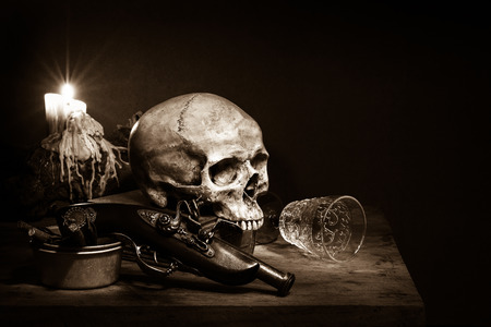 Still life, skull with ancient gun under candle light photo