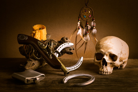 Still life with human skull , candle with wax tear, horseshoes and ancient pistol , ancient pistol and flask photo