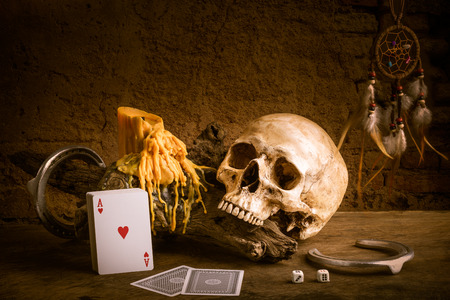 Still life with human skull , candle with wax tear, horseshoe, dream catcher, dice and playing card on grunge brick wall photo