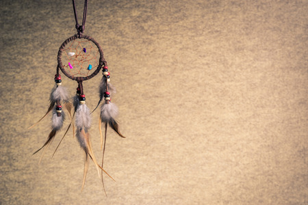 Leather dream catcher on sepia tone background, left copy space photo