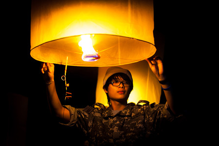 Man in soldier uniform holding floating fire lantern ready launch to the air in Loy Krathong festival photo