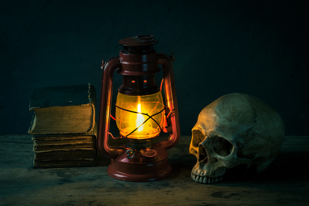 Still life with human skull and old fashioned vintage kerosene oil lantern lamp burning with a soft glow light on aged wooden floor Stock Photo