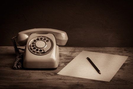 Still life with retro telephone and brown paper on wooden table photo
