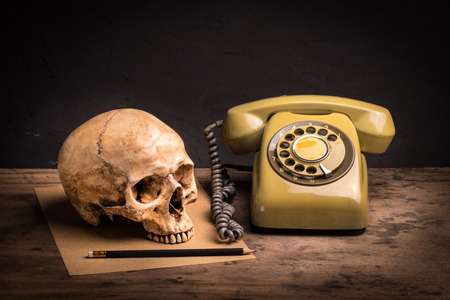 Still life with human skull, retro telephone and brown paper on wooden table photo