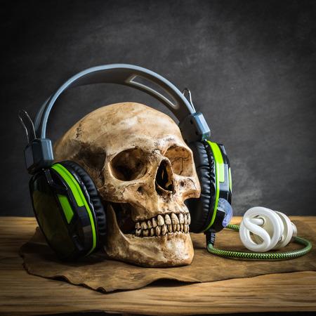 partes del cuerpo humano: Naturaleza muerta con cráneo humano con los auriculares