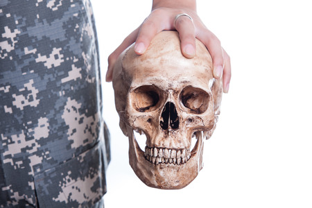Human skull in the soldier hand on isolated white background photo
