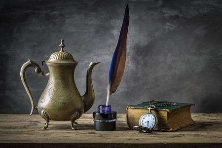 Still life with vintage antique pocket watch, brass tea pot and  grunge book