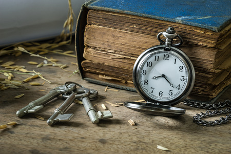 Vintage antique pocket watch and keys on grunge book background photo