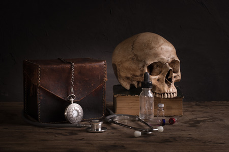 Still life with human skull on old book, stethoscope and pocket watch photo