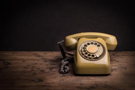 木製のテーブルにレトロな電話のある静物