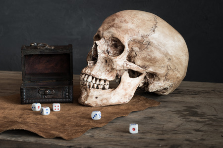 Still life with human skull, dices and leather box photo