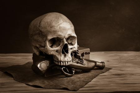 Stll life with human skull and ancient pistol photo