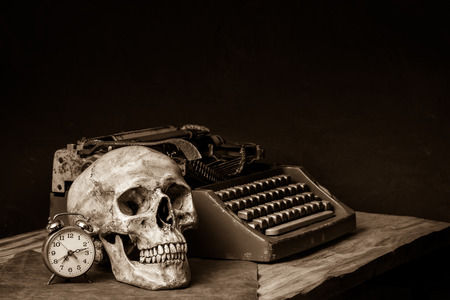 still life with human skull, old typewriter and alarm clock ]on wooden table