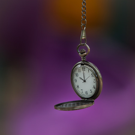 Open pocket watch on colorful soft focus background