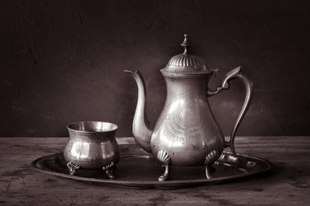 Still life with antique teapot on wooden table photo