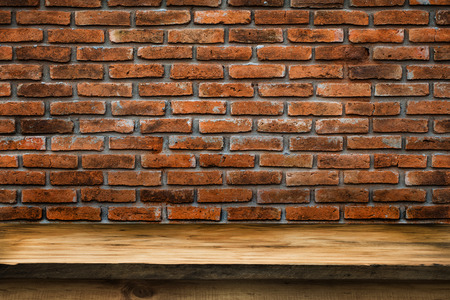 mpty wooden deck table with vintage brick wall pattern. Ready for product display montage. photo