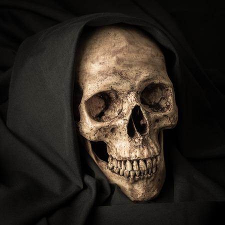 Human skull in black hood as image of death photo