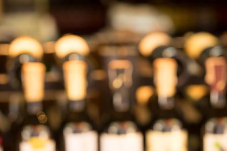 Line of wine bottles display in store, soft focus