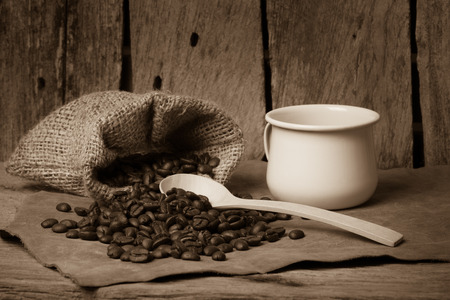 coffee beans on wooden table with white cup and wooden spoon photo