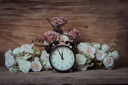past midnight: still life, vintage alarm clock with flowers on wooden table