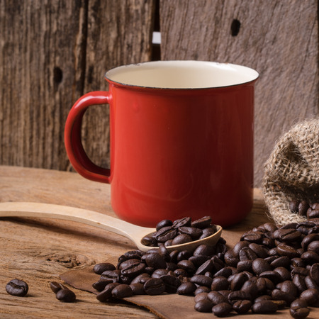Still life, coffee bean on wooden table with red cup and wooden spoon photo