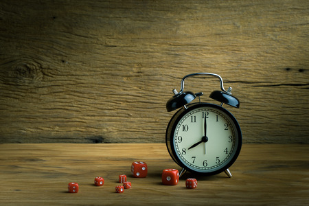 Still life with alarm clock and red dices on the wooden table