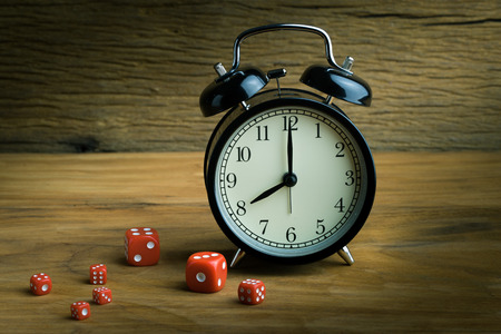 Still life with alarm clock and red dices on the wooden table photo