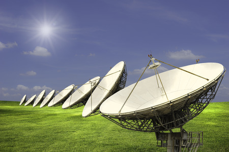 Satellite disks line in wide meadow with clouds in blue sky in sunny day photo