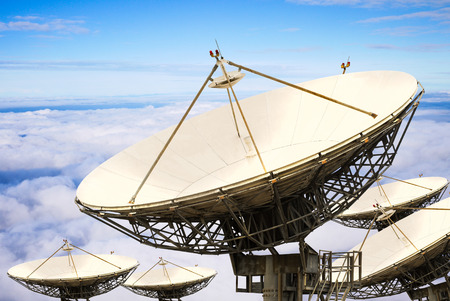 Satellite dishes over the white clouds and blue sky photo