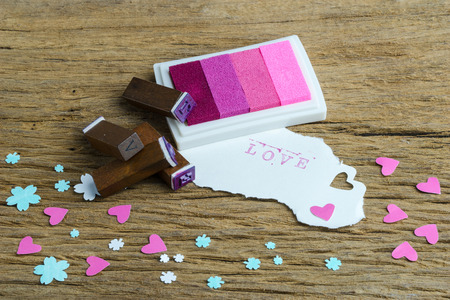e ink: Rubber stamp with letters L O V E with ink pad on wooden table Stock Photo