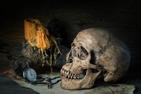 Still life with human skull on old map and vintage pocket watch near yellow candle on the log photo