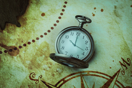 Vintage antique pocket watch on old map background photo