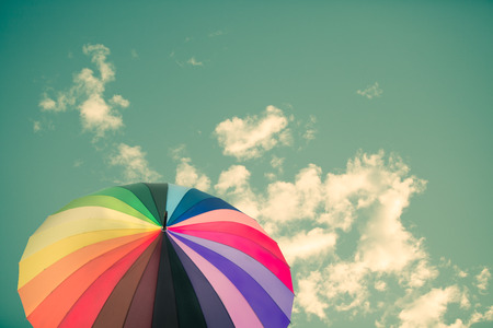 Rainbow umbrella on sky background, vintage style Stock Photo