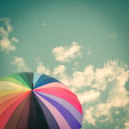 lluvia paraguas: Paraguas del arco iris en el cielo de fondo, estilo vintage
