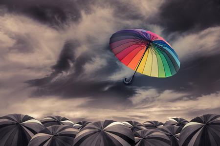 Paraguas del arco iris volar fuera de la masa de paraguas negros Foto de archivo - 36850545