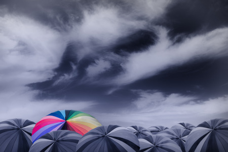 thinkers: rainbow umbrella in the mass of black umbrellas Stock Photo