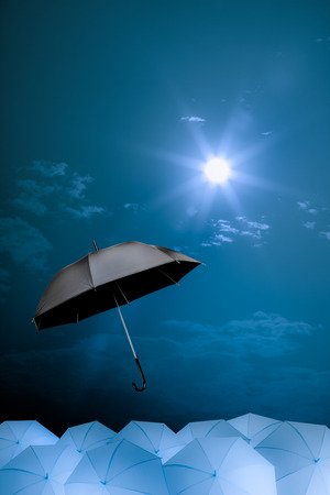 black umbrella fly out from the mass of blue umbrellas photo
