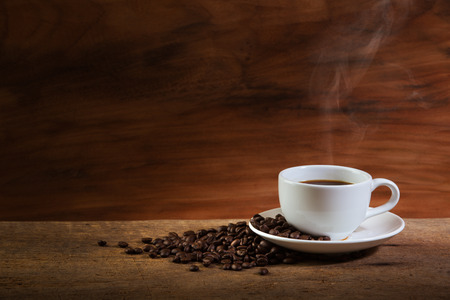 seeds coffee: Coffee cup and coffee beans with stream on old wooden background Stock Photo