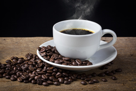Coffee cup and coffee beans with stream on old wooden background Banque d'images